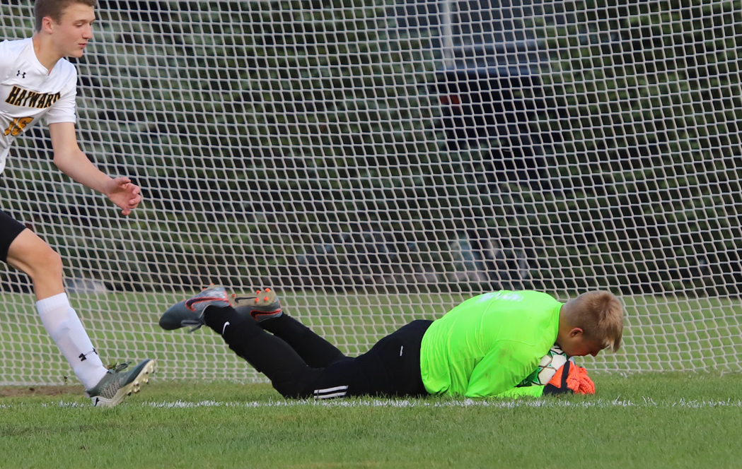 Keeper Gavin Ostermann covers the ball after a shot on goal by Hayward.