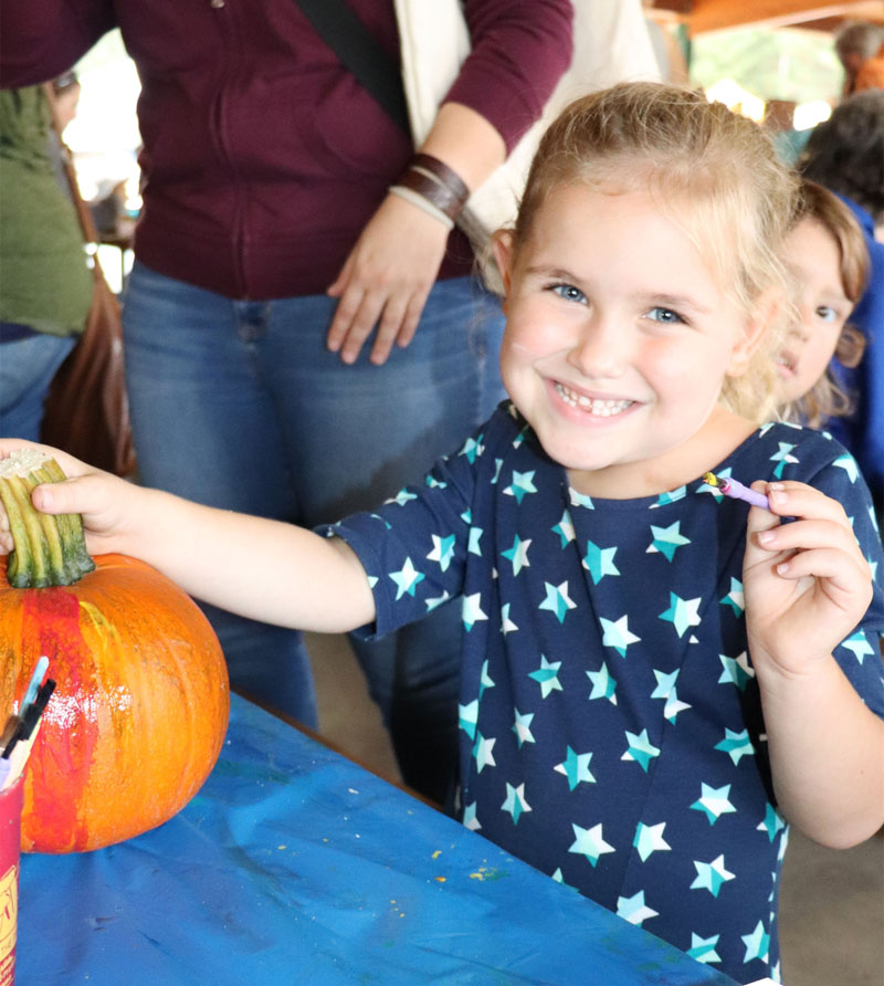Ellie paints her pumpkin at the kids' table at Colorama in St. Germain.